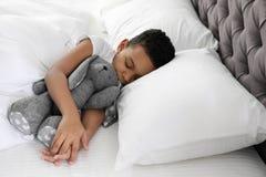 Gullig liten afrikansk amerikanpojke med att sova för leksakkanin arkivfoton