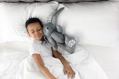 Gullig liten afrikansk amerikanpojke med leksakkanin som sover i säng royaltyfri fotografi