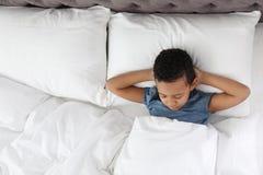 Gullig liten afrikansk amerikanpojke som sover i s?ng arkivfoto