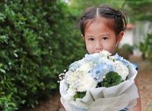 Gullig liten asiatisk barnflicka med buketten av blommor i trädgården arkivbild