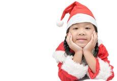 Gullig liten asiatisk flicka i röda den isolerade santa hatten Arkivbild