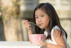 Gullig liten asiatisk flicka som äter sädesslag i morgon Royaltyfri Bild