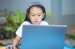 Gullig liten asiatisk flicka som använder bärbara datorn arkivfoto
