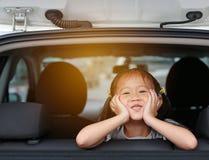 Gullig liten asiatisk flicka som ser kameran fr?n f?nstret av bilen med str?lar av solljus royaltyfria bilder