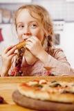 Gullig liten blond barnflicka som äter italiensk pizza för pizzamellanmål royaltyfria bilder