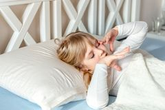 Gullig liten blond caucasian flickauppvaknande på säng i morgon Barnvak upp tidigt som går till skolan Sträckning och gäspa Sunt arkivbild