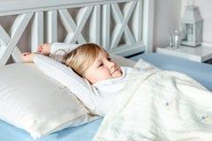Gullig liten blond caucasian flickauppvaknande på säng i morgon Barnvak upp tidigt som går till skolan Sträckning och gäspa Sunt arkivbilder