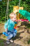 Gullig liten blond pojke som svänger på utomhus- lekplats för gungor Royaltyfria Bilder