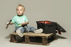 Gullig liten blond pojkeinnehavhammare, Arkivfoton