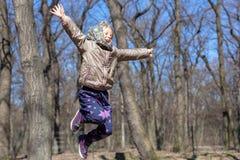 Gullig liten blond ungeflicka som har rolig det fria Barn i tillfällig sportkläder och sjalettbanhoppninghöjdpunkt från trädstubb royaltyfria foton