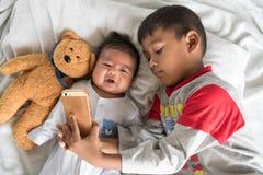 Gullig liten broder Using Mobile Taking Selfie med hans broder Fotografering för Bildbyråer