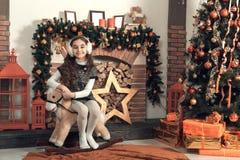 Gullig liten brunettflicka med långt hårsammanträde på en leksakhäst Arkivfoto