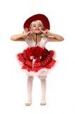 Gullig liten caucasian flicka som bär den röda kjolen, t-skjortan med blommor och cowboyhatten som isoleras på vit bakgrund Hon d Royaltyfri Bild