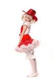 Gullig liten caucasian flicka som bär den röda kjolen, t-skjortan med blommor och cowboyhatten som isoleras på vit bakgrund Hon d Royaltyfria Foton