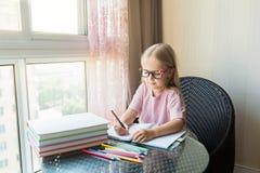 Gullig liten caucasian flicka som g?r l?xa och skriver ett papper Ungen tycker om att l?ra med hemmastadd lycka Klyftigt, utbildn royaltyfri foto