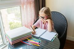 Gullig liten caucasian flicka som g?r l?xa och skriver ett papper Ungen tycker om att l?ra med hemmastadd lycka Klyftigt, utbildn royaltyfria foton