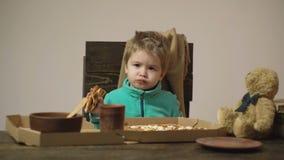 Gullig liten caucasian pojke som äter pizza på trätabellen som det finns den pizzaasken, skeden, maträtten och björnen som på iso lager videofilmer