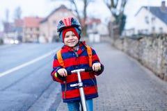 Gullig liten förskole- ungepojkeridning på sparkcykelridning till skolan Royaltyfria Bilder