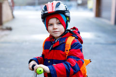 Gullig liten förskole- ungepojkeridning på sparkcykelridning till skolan Arkivbild
