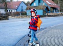 Gullig liten förskole- ungepojkeridning på sparkcykelridning till skolan Arkivfoto