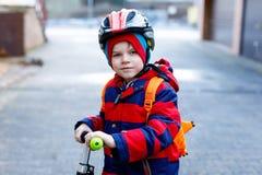 Gullig liten förskole- ungepojkeridning på sparkcykelridning till skolan Royaltyfri Foto