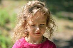 Gullig liten flicka, allvarlig blick, lockigt hår, solig sommarstående Arkivfoto