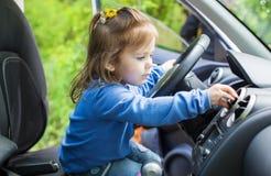 Gullig liten flicka bak hjulet Arkivbild