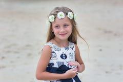Gullig liten flicka för stående med långt hår och en krans av blommor Arkivfoton
