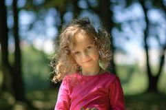 Gullig liten flicka, gladlynt blick, lockigt hår, trevligt leende, solig sommarstående Arkivbilder