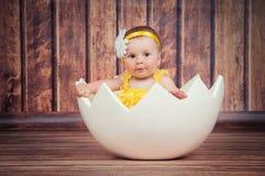 Gullig liten flicka i äggkorgen arkivbilder