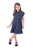 Gullig liten flicka i att posera för grov bomullstvillklänning som isoleras på vit Royaltyfria Foton