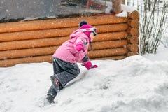 Gullig liten flicka i den rosa sportdräkten som har gyckel som utomhus spelar under snöfall i vinter Barn övervintrar säsongsbeto arkivfoto