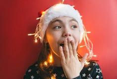 Gullig liten flicka i den Santa Claus hatten med girlanden på röd bakgrund arkivfoton