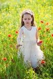 Gullig liten flicka i en äng med lösa blommor Royaltyfri Bild