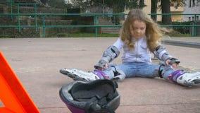 Gullig liten flicka i en hjälm och ett skyddande kugghjul lager videofilmer