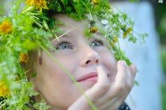 Gullig liten flicka i en krans av att drömma för blommor Arkivbilder