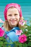 Gullig liten flicka i en trädgård på en bakgrund av turkosstaketet Royaltyfri Foto