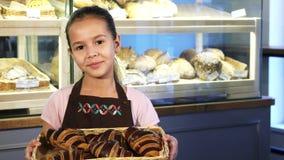 Gullig liten flicka i ett förkläde som arbetar på bagerit som rymmer en korg med bakelse fotografering för bildbyråer