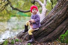 Gullig liten flicka i ett rött lock nära sjön på Royaltyfri Bild
