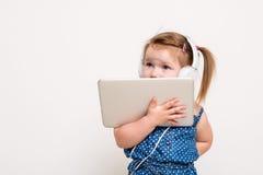 Gullig liten flicka i hörlurar som lyssnar till musik genom att använda en minnestavla och le på vit bakgrund arkivbild