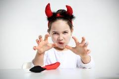 Gullig liten flicka i imp Arkivfoton