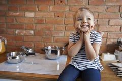 Gullig liten flicka i köket arkivfoton