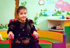 Gullig liten flicka i rullstol på rehabiliteringmitten för ungar med speciala behov arkivbild