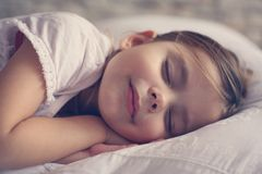 Gullig liten flicka i säng royaltyfria bilder
