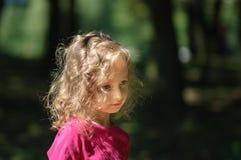 Gullig liten flicka i skogen, allvarlig blick, lockigt hår, solig sommarstående Royaltyfri Fotografi