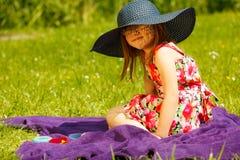 Gullig liten flicka i stor hatt som låtsar för att vara dam Royaltyfria Foton