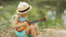 Gullig liten flicka i sugrörhatten som spelar på leksaken stock video