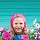 Gullig liten flicka i trädgård på bakgrund av turkosstaketet Arkivfoto