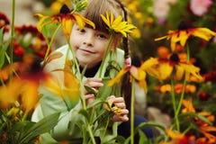 Gullig liten flicka i tr?dg?rden med blommor royaltyfri bild