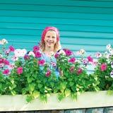 Gullig liten flicka i trädgård på bakgrund av turkosstaketet Royaltyfria Bilder